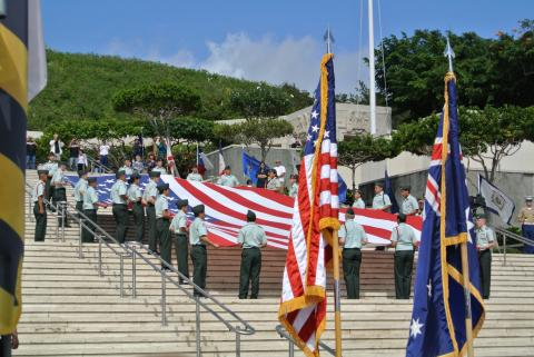 Members of the military fold a large American flag on the steps of the Honolulu Memorial, Veterans Day 2011.