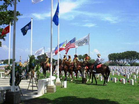 Men on horses are between the ceremony area and the plot area.