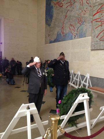 Two men stand and salute after laying floral wreaths.