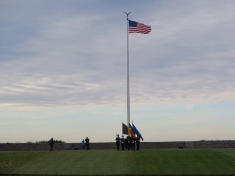 In the distance, an honor guard is seen at the flag pole.