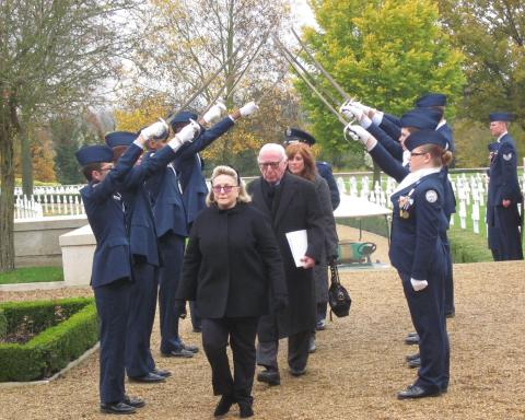 Four VIPs walk under sword-bearing men and women in uniform during 2012 Veterans Day ceremony.