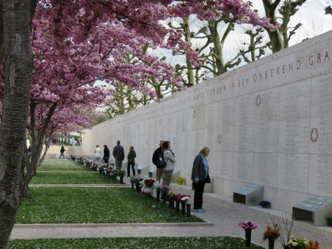 Visitors stand near the Walls of the Missing looking at photos.