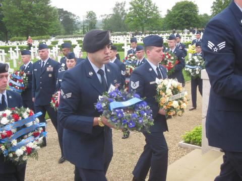 Members of the Air Force walk with small floral wreaths.