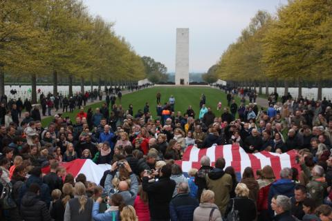 People gather around a large American flag.