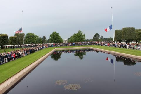 Attendees sit around the reflecting pool, with the American and French flag at half mast in the background.