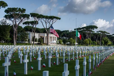 Rows of headstones with American and Italian flags cover the landscape in front of the memorial building.