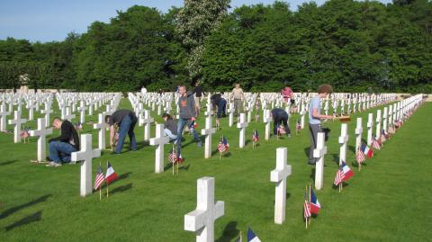 Volunteers place American and French flags in front of every headstone.